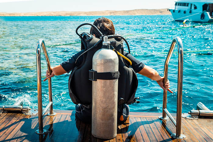 Diver in gear sitting on the deck