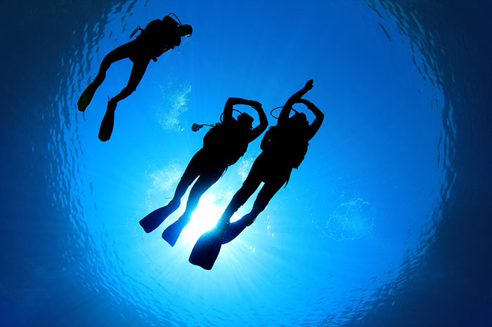 Three divers from shot from underneath with sky above
