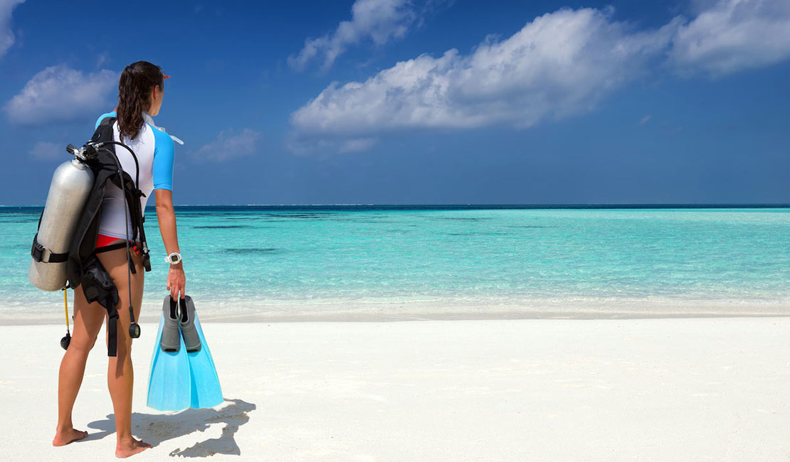 Person in scuba gear standing on the beach