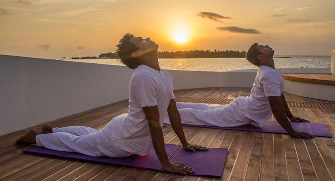 Two people performing yoga exercise on a boat